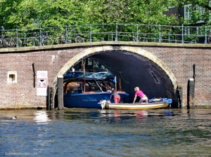 Their outboard motor out of gas, two girls try to get out of the way of a canal tour boat.