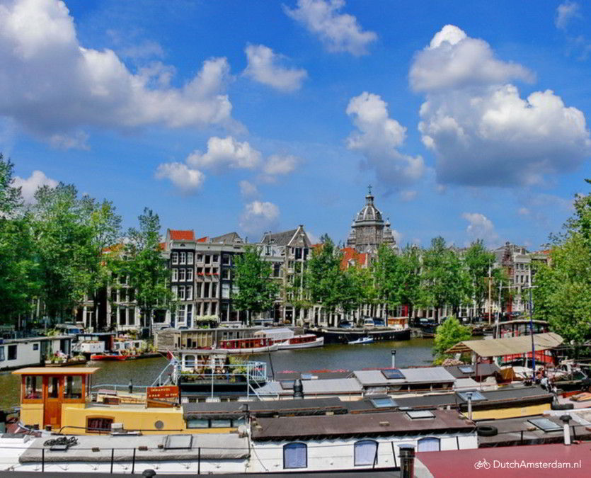 Typical Amsterdam summer weather: sunny, blue skies, some cumulus clouds. Shown is the Waaleilandgracht, a canal in downtown Amsterdam.