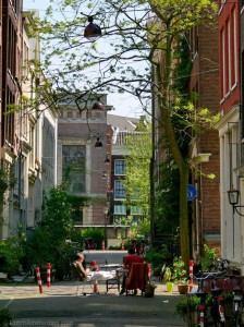 Locals enjoying the sun at the intersection of two car-free streets in Amsterdam